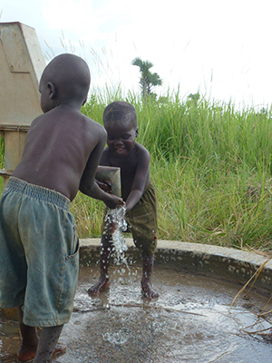 kids pumping clean water from newly repaired well
